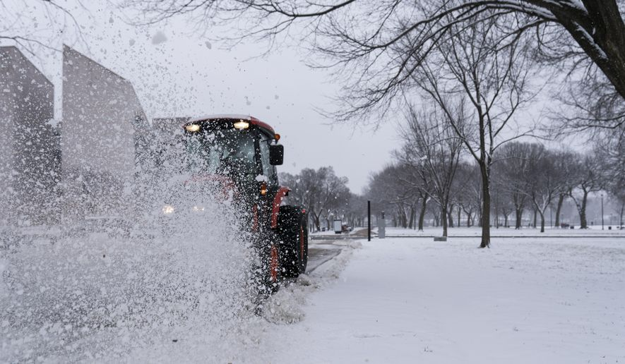 A machine is used to brush snow off the sidewalk on the National Mall, Sunday, Jan. 31, 2021, in Washington. (AP Photo/Alex Brandon) **FILE**