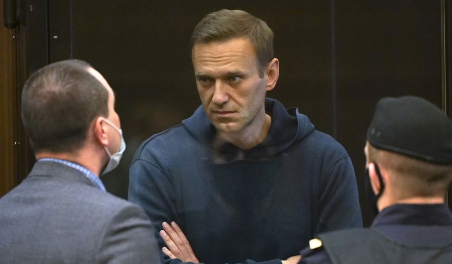In this handout photo provided by Moscow City Court Russian opposition leader Alexei Navalny (center) talks to one of his lawyers, left, while standing in the cage during a hearing to a motion from the Russian prison service to convert the suspended sentence of Navalny from the 2014 criminal conviction into a real prison term in the Moscow City Court in Moscow, Russia, Tuesday, Feb. 2, 2021. (Moscow City Court via AP)