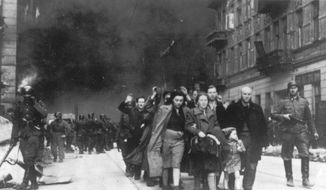 In this 1943 photo, a group of Polish Jews are led away for deportation by German SS soldiers, during the destruction of the Warsaw Ghetto by German troops after an uprising in the Jewish quarter. Two Polish historians are facing a libel trial for a scholarly examination of Polish behavior during World War II, a case whose outcome is expected to determine the fate of independent Holocaust research under Poland's nationalist government. A verdict is expected Feb. 9. (AP Photo, B/W File)