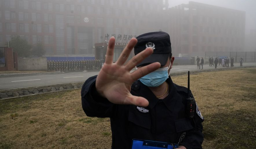 A security person moves journalists away from the Wuhan Institute of Virology after a World Health Organization team arrived for a field visit in Wuhan in China's Hubei province on Wednesday, Feb. 3, 2021. The WHO team is investigating the origins of the coronavirus pandemic has visited two disease control centers in the province. (AP Photo/Ng Han Guan)