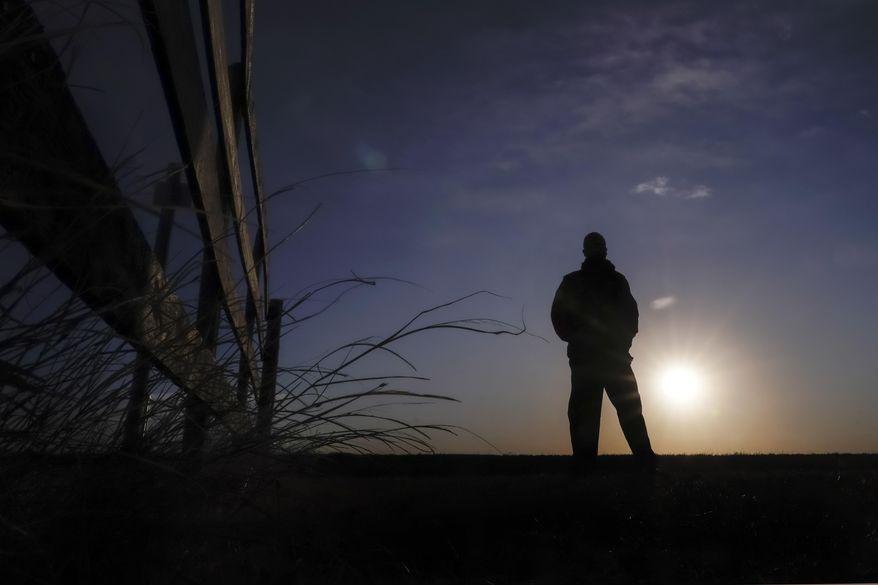 """Lateef Dowdell watches the sunrise from what remains of land once belonging to his uncle Gil Alexander, who was the last active Black farmer in the community of Nicodemus, Kan., Thursday, Jan. 14, 2021. Dowdell moved back to Nicodemus, a settlement founded by former slaves known as """"exodusters"""" in the 1870s, several years earlier to take over the farm after his uncle died, but soon after lost most of the land when the bank foreclosed. New legislation in Congress aims to remedy historical inequities in government farm programs that have helped reduce the number of Black farmers in the United States from about a million in 1920 to less than 50,000 today. (AP Photo/Charlie Riedel)"""