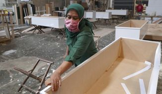 A worker assembles special coffins for the victims of COVID-19 at a factory in Tangerang, Indonesia, Tuesday, Feb. 2, 2021. The number of coronavirus-related cases and deaths in the world's fourth most populous country has been rising since early December, prompting several regional governments on the islands of Java and Bali to reimpose restrictions on public activity. (AP Photo/Tatan Syuflana)