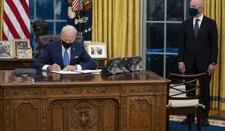 Secretary of Homeland Security Alejandro Mayorkas looks on as President Joe Biden signs an executive order on immigration, in the Oval Office of the White House, Tuesday, Feb. 2, 2021, in Washington. (AP Photo/Evan Vucci)