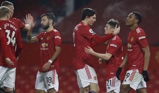 Manchester United players celebrate after Anthony Martial, right, scoring his side's eighth goal during the English Premier League soccer match between Manchester United and Southampton, at the Old Trafford stadium in Manchester, England, Tuesday, Feb. 2, 2021. (Phil Noble/Pool via AP)