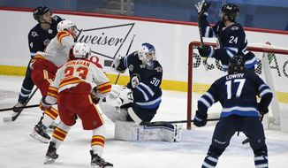Winnipeg Jets' Derek Forbort (24) reaches for a loose puck behind goaltender Laurent Brossoit (30) after a Calgary Flames shot during the third period of an NHL hockey game, Tuesday, Feb. 2, 2021 in Winnipeg, Manitoba. (Fred Greenslade/The Canadian Press via AP)