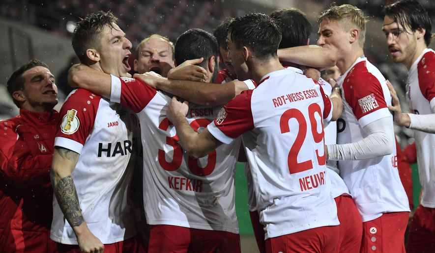 Essen's Oguzhan Kefkir, second from left, celebrates after scoring his side's first goal during the German Soccer Cup 3rd round match between RW Essen and Bayer Leverkusen in Essen, Germany, Tuesday, Feb. 2, 2021. (AP Photo/Martin Meissner, Pool)