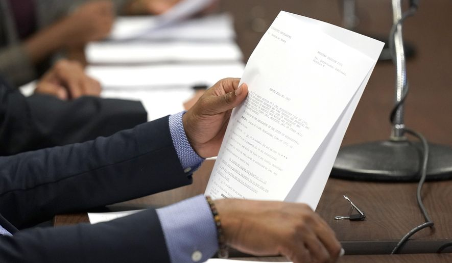 A member of the Senate Corrections Committee reviews proposed legislation during a meeting, Tuesday, Jan. 26, 2021, at the Capitol in Jackson, Miss. (AP Photo/Rogelio V. Solis)