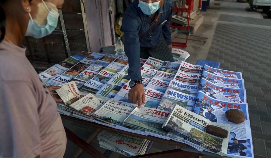 A newspaper seller points at a front-page of a newspaper in Yangon, Myanmar, Tuesday, Feb. 2, 2021. Hundreds of members of Myanmar's Parliament remained confined inside their government housing in the country's capital on Tuesday, a day after the military staged a coup and detained senior politicians including Nobel laureate and de facto leader Aung San Suu Kyi. (AP Photo/Thein Zaw)