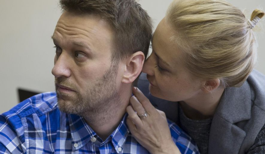 In this Thursday, April 23, 2015 file photo, Russian opposition activist Alexei Navalny and his wife Yulia talk in a courtroom before the hearing in Moscow, Russia. Moscow is bracing for more protests seeking the release of jailed opposition leader Alexei Navalny, who faces a court hearing Tuesday. Navalny was jailed last month and faces years in prison. (AP Photo/Pavel Golovkin, File)