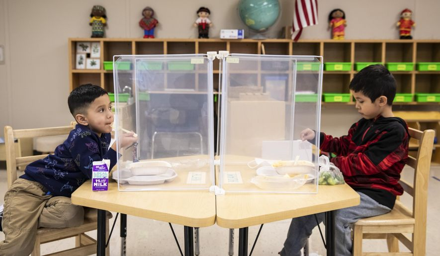 FILE - In this Jan. 11, 2021, file photo, preschool students eat lunch at Dawes Elementary in Chicago. Pressure is building on school systems around the U.S. to reopen classrooms to students who have been learning online for nearly a year, pitting politicians against teachers who have yet to be vaccinated against COVID-19. (Ashlee Rezin Garcia/Chicago Sun-Times via AP, Pool, File)