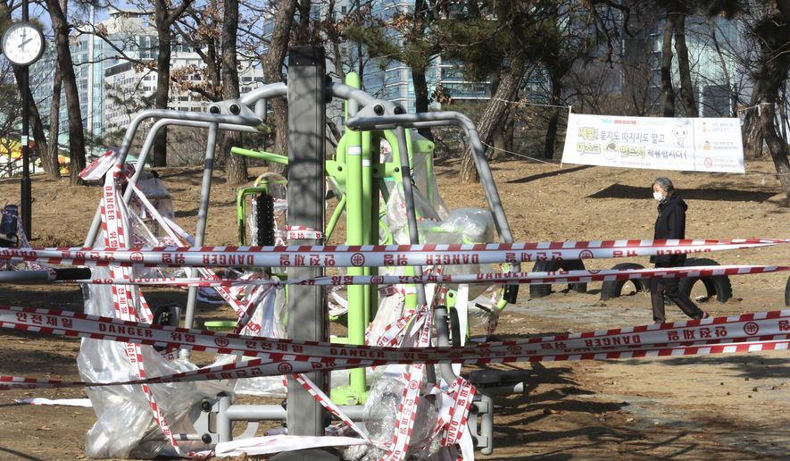 Banned public sports facilities are taped off according to social distancing rules at a park in Goyang, South Korea, Tuesday, Feb. 2, 2021. (AP Photo/Ahn Young-joon)