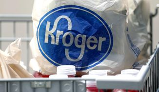 FILE- In this June 15, 2017, file photo, bagged purchases from a Kroger grocery store sit in a shopping cart in Flowood, Miss. Kroger Co. will close two supermarkets in Southern California in response to a local ordinance requiring extra pay for certain grocery employees working during the coronavirus pandemic. The decision announced by the company Monday, Feb. 1, 2021, follows a unanimous vote last month by the Long Beach City Council mandating a 120-day increase of $4 an hour for employees of supermarkets with at least 300 employees nationwide and more than 15 in Long Beach. (AP Photo/Rogelio V. Solis, File)