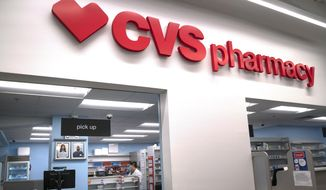In this March 17, 2020, file photo, Pharmacist Evelyn Kim, wears a mask and gloves at the CVS pharmacy at Target in the Tenleytown area of Washington. The Biden administration will begin providing COVID-19 vaccines to U.S. pharmacies, including CVS, part of its plan to ramp up vaccinations as new and potentially more serious virus strains are starting to appear. (AP Photo/Carolyn Kaster) **FILE**