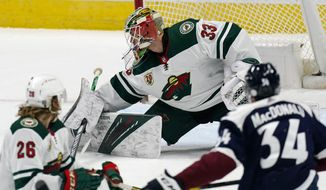 Minnesota Wild goaltender Cam Talbot, back, makes a stick save of a shot as right wing Gerald Mayhew, front left, and Colorado Avalanche defenseman Jacob MacDonald watch during the first period of an NHL hockey game Tuesday, Feb. 2, 2021, in Denver. (AP Photo/David Zalubowski)