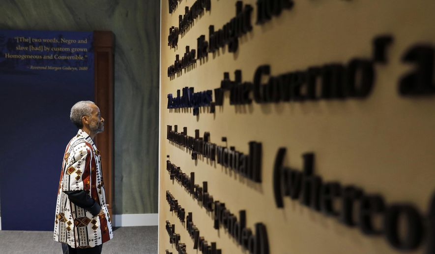 In this Aug. 24, 2019, photo, Jerome Jones explores inside the Fort Monroe Visitor And Education Center during the First African Landing Commemorative Ceremony at Fort Monroe, Va. Officials observed the arrival of enslaved Africans 400 years earlier to what is now Virginia. Proposals in Arkansas, Iowa and Mississippi would prohibit schools from using a New York Times project that focused on slavery's legacy. (Jonathon Gruenke/The Daily Press via AP) **FILE**