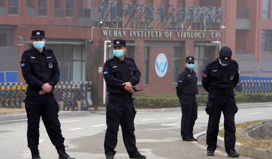 Security personnel manned the entrance of the Wuhan Institute of Virology during a visit this week by a team from the World Health Organization. (Associated Press) ** FILE **
