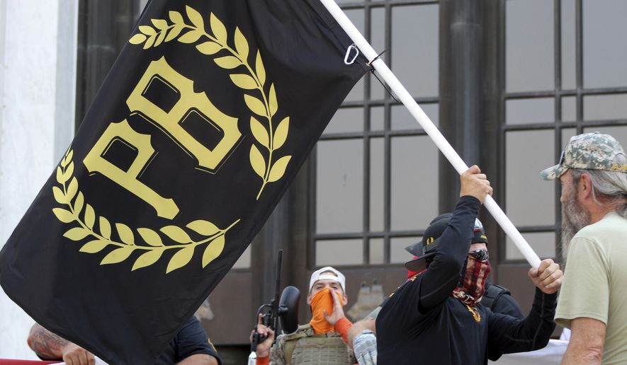 In this Sept. 7, 2020, file photo, a protester carries a Proud Boys banner, a right-wing group, while other members start to unfurl a large U.S. flag in front of the Oregon State Capitol in Salem, Ore. The Proud Boys are the target of a new lawsuit filed by the NAACP, which alleges the group to have violated the Ku Klux Klan Act in its actions in the Jan. 6 riot at the U.S. Capitol. (AP Photo/Andrew Selsky, File)  **FILE**