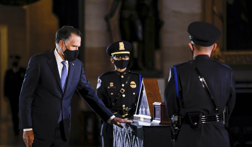 Sen. Mitt Romney, R-Utah, pays respect to the late U.S. Capitol Police officer Brian Sicknick as an urn with his cremated remains lies in honor on a black-draped table at the center of the Capitol Rotunda, Wednesday, Feb. 3, 2021, in Washington. (Carlos Barria/Pool via AP)