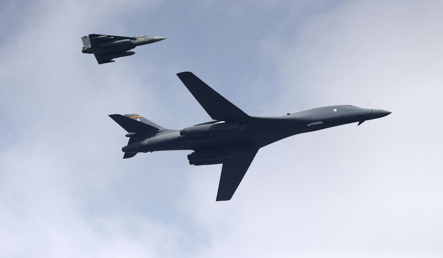 A U.S. Air Force B-1B Lancer bomber, right, flies with an Indian Air Force light combat aircraft Tejas on the inaugural day of Aero India 2021 at Yelahanka air base in Bengaluru, India, Wednesday, Feb. 3, 2021. Aero India is a biennial event with flying demonstrations by stunt teams and militaries and commercial pavilions where aviation companies display their products and technology. (AP Photo/Aijaz Rahi)