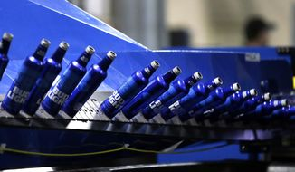 FILE - In this Friday, April 8, 2016, file photo, aluminum Bud Light bottles move along a conveyor at a plant manufacturing 16-ounce Budweiser and Bud Light aluminum bottles for Anheuser-Busch, in Arnold, Mo.  Anheuser-Busch says, Wednesday, Feb. 3, 2021,  it's investing $1 billion over the next two years to modernize its U.S. facilities. Nearly half that amount will go to the company's 12 major U.S. breweries. Anheuser-Busch said it will spend $100 million for new can lines and $100 million on solar panel installation and other sustainability measures.  (AP Photo/Jeff Roberson, File)
