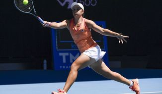 Australia's Ash Barty makes a forehand return to Marie Bouzkova of the Czech Republic during a tuneup event ahead of the Australian Open tennis championships in Melbourne, Australia, Wednesday, Feb. 3, 2021. (AP Photo/Andy Brownbill)