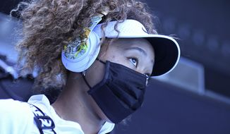 Japan's Naomi Osaka walks out onto court for her match against Britain's Katie Boulter during a tuneup event ahead of the Australian Open tennis championships in Melbourne, Australia, Wednesday, Feb. 3, 2021. (AP Photo/Andy Brownbill)