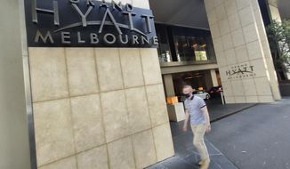 A pedestrian walks outside the Grand Hyatt hotel in central Melbourne, Australia, Thursday, Feb. 4, 2021. All competition at six Australian Open tuneup events scheduled for Thursday was called off after a worker at one of the tournaments' Melbourne quarantine hotels tested positive for COVID-19. (AP Photo/Hamish Blair)