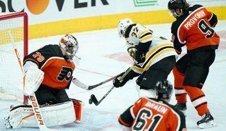 Boston Bruins' Patrice Bergeron (37) scores the game-winning goal past Philadelphia Flyers' Carter Hart (79) during overtime in an NHL hockey game, Wednesday, Feb. 3, 2021, in Philadelphia. (AP Photo/Matt Slocum)