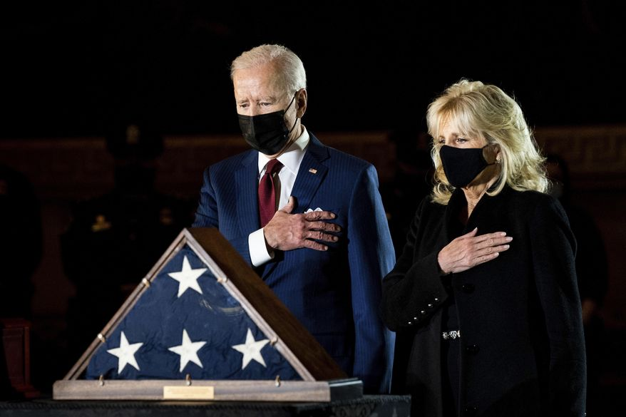 President Joe Biden and first lady Jill Biden pay their respects to the late U.S. Capitol Police officer Brian Sicknick as an urn with his cremated remains lies in honor on a black-draped table at the center of Capitol Rotunda, Tuesday, Feb. 2, 2021, in Washington. (Erin Schaff/The New York Times via AP, Pool)