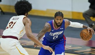 Los Angeles Clippers' Paul George, right, drives to the basket against Cleveland Cavaliers' Jarrett Allen in the second half of an NBA basketball game, Wednesday, Feb. 3, 2021, in Cleveland. The Clippers won 121-99.(AP Photo/Tony Dejak)