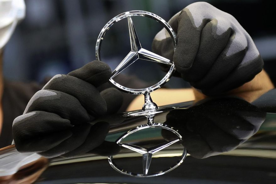 """FILE - In this Thursday, April 30, 2020 file photo, an employee attaches a Mercedes emblem as he works on a Mercedes-Benz S-class car at the Mercedes plant in Sindelfingen, Germany. German automaker Daimler said it will split itself into two independent companies by spinning off its truck and bus division. The Stuttgart-headquartered company said Wednesday, Feb. 3, 2021 that a significant majority stake in the truck business would be distributed to current shareholders, and that Daimler would """"at the appropriate time"""" be renamed Mercedes-Benz, the brand name under which it sells luxury cars.  (AP Photo/Matthias Schrader, file)"""