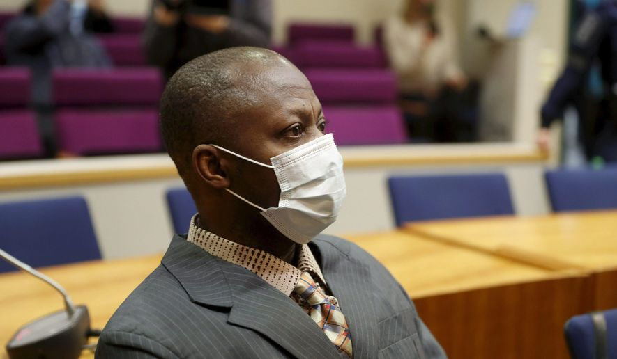 Sierra Leonean national Gibril Massaquoi, 51, wears a face mask as he attends his trial at the Pirkanmaa District Court in Tampere, Finland, Wednesday Feb. 3, 2021, accused of committing war crimes during Liberia's second civil war two decades ago.  Massaquoi faces several charges including dozens of murders, eight rapes as well as aggravated war crimes and aggravated human rights violations during Liberia's 1999-2003 war. (Kalle Parkkinen/Lehtikuva via AP)