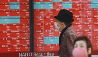 A man looks at an electronic stock board of a securities firm in Tokyo, Wednesday, Feb. 3, 2021. Asian shares opened mostly higher on Wednesday although markets in Shanghai and Hong Kong were lower. (AP Photo/Koji Sasahara)