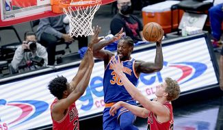 New York Knicks' Julius Randle (30) looks to pass between Chicago Bulls' Thaddeus Young, left, and Lauri Markkanen during the first half of an NBA basketball game Wednesday, Feb. 3, 2021, in Chicago. (AP Photo/Charles Rex Arbogast)