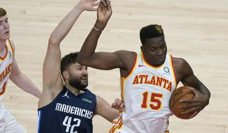 Atlanta Hawks center Clint Capela (15) and Dallas Mavericks forward Maxi Kleber (42) compete for a rebound during the first half of an NBA basketball game Wednesday, Feb. 3, 2021, in Atlanta. (AP Photo/John Bazemore)