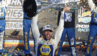 """Chase Elliott holds up the season championship trophy as he celebrates with his race crew in Victory Lane after winning the NASCAR Cup Series auto race at Phoenix Raceway in Avondale, Ariz., in this Sunday, Nov. 8, 2020, file photo. NASCAR is being heavily promoted by a broadcast partner as about to embark on """"The Best Season Ever"""" and on paper that could be true. NASCAR this year will race on dirt for the first time since 1970, the schedule includes a whopping seven road courses and five venues new to the Cup Series. Michael Jordan and Pitbull are among new team owners entering the sport in 2021 and Chase Elliott, NASCAR's most popular driver, is the reigning champion. (AP Photo/Ralph Freso, File) **FILE**"""