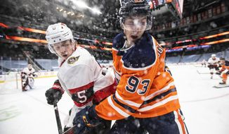 Edmonton Oilers' Ryan Nugent-Hopkins (93) and Ottawa Senators' Mike Reilly (5) vie for the puck during the second period of an NHL hockey game Tuesday, Feb. 2, 2021, in Edmonton, Alberta. (Jason Franson/The Canadian Press via AP)