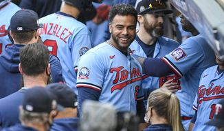 FILE - In this Sept. 27, 2020, file photo, Minnesota Twins' Nelson Cruz, center, smiles in the dugout after the Twins clinched the AL Central championship with the Chicago White Sox's loss during the tenth inning of a baseball game in Minneapolis. The Minnesota Twins are bringing back designated hitter Nelson Cruz on a one-year, $13 million contract, according to a person with knowledge of the negotiations. The agreement was reached late Tuesday and confirmed Wednesday, Feb. 3, 2021, to The Associated Press on condition of anonymity because the deal was pending completion of a physical exam.(AP Photo/Craig Lassig, File)