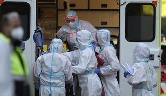 FILE - In this file photo dated Friday, Nov. 6, 2020, healthcare workers move a COVID-19 patient to the Motol hospital in Prague, Czech Republic. The hospital in Prague has admitted five patients in serious condition from other hospitals that were overrun due to the coronavirus pandemic. Reaching a milestone of one million confirmed cases, the battle against the pandemic is far from over in the Czech Republic. Amid warnings by experts against new contagious virus variants, one of the hardest hit European countries has been trying to avoid the mistakes of the past when soaring infections almost caused the collapse of the struggling health system. (AP Photo/Petr David Josek, FILE)