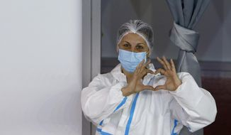 A medical worker wearing protective gear gestures as people wait to receive the COVID-19 vaccine, at Belgrade Fair makeshift vaccination center, in Belgrade, Serbia, Monday, Jan. 25, 2021. Serbia were the first European country to receive the Chinese Sinopharm's vaccine for mass inoculation programmes. (AP Photo/Darko Vojinovic)
