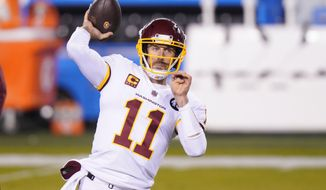 """FILE - Washington Football Team quarterback Alex Smith warms up before an NFL football game against the Philadelphia Eagles in Philadelphia, in this Sunday, Jan. 3, 2021, file photo. Washington's biggest offseason need is to figure out its quarterback situation. Trade for DeShaun Watson? Sign Cam Newton? Roll with Alex Smith and Kyle Allen? Coach Ron Rivera says """"nothing is off the table."""" (AP Photo/Chris Szagola, File)"""