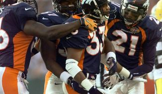 FILE - In this file photo dated Sunday, Jan. 25, 1998, Denver Broncos Dedrick Dodge (33) celebrates with teammates Randy Hilliard (21) and Anthony Lynn (37) after he stopped Green Bay Packers' Antonio Freeman on a kickoff return in the second quarter of Super Bowl XXXII, at San Diego's Qualcomm Stadium.  The year 2021 marks the 30th anniversary of the World League of American Football, and Dedrick Dodge joined the London Monarchs and helped them win the first World Bowl in 1991. (AP Photo/Susan Ragan, FILE)