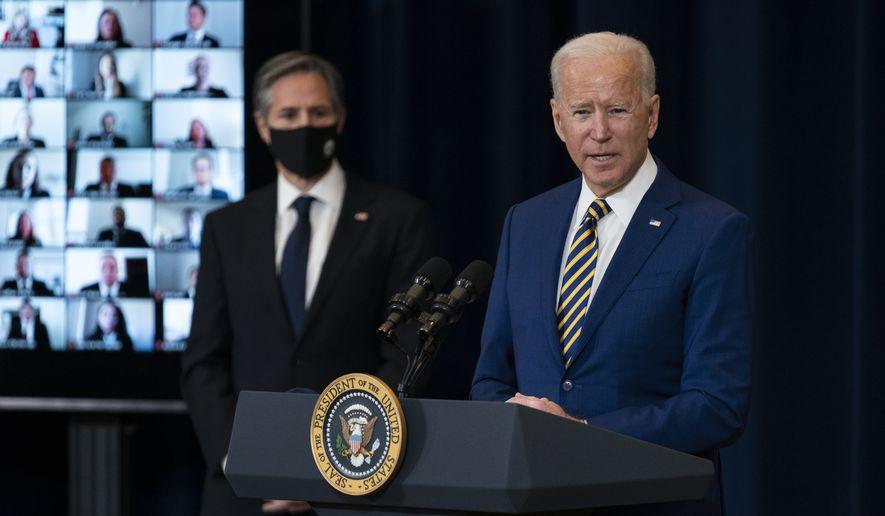Secretary of State Anthony Blinken listens as President Joe Biden delivers remarks to State Department staff, Thursday, Feb. 4, 2021, in Washington. (AP Photo/Evan Vucci)