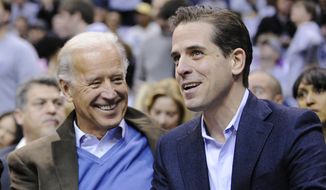 Then Vice President Joe Biden, left, and his son Hunter Biden appear at the Duke Georgetown NCAA college basketball game in Washington on Jan. 30, 2010. (AP Photo/Nick Wass, File)  **FILE**