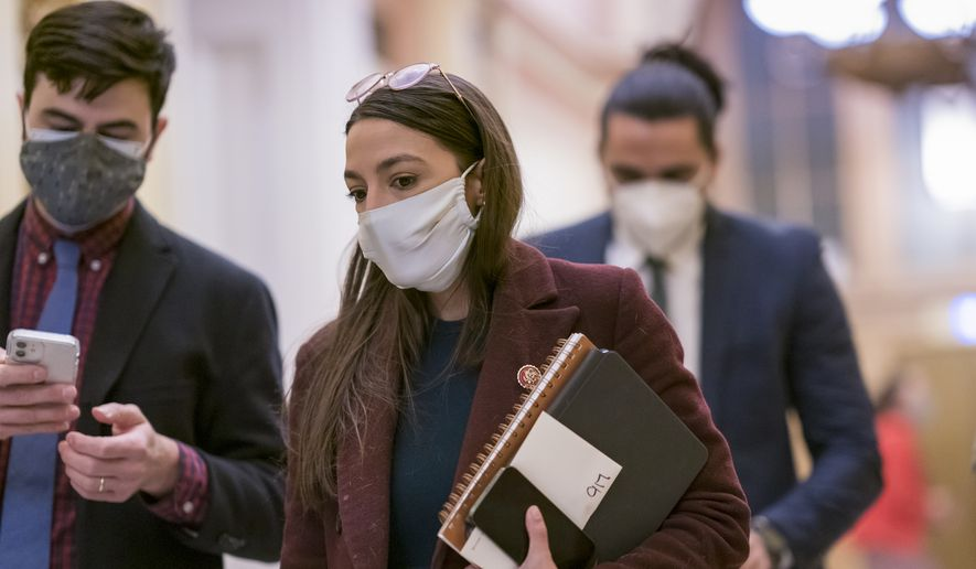 Rep. Alexandria Ocasio-Cortez, D-N.Y., arrives at the House chamber to vote on a resolution to strip Rep. Marjorie Taylor Greene, R-Ga., from her committee assignments because of her extremist views, at the Capitol in Washington, Thursday, Feb. 4, 2021. (AP Photo/J. Scott Applewhite)