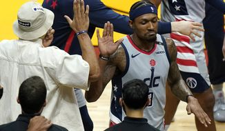 Washington Wizards guard Russell Westbrook, left, high-fives guard Bradley Beal, right during the second half of an NBA basketball game against the Miami Heat, Wednesday, Feb. 3, 2021, in Miami. The Wizards won 103-100. (AP Photo/Lynne Sladky)