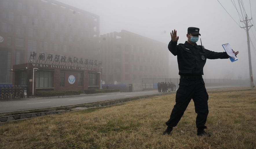 A security official moves journalists away from the Wuhan Institute of Virology after a World Health Organization team arrived for a field visit in Wuhan in China's Hubei province on Wednesday, Feb. 3, 2021. The WHO team is investigating the origins of the coronavirus pandemic has visited two disease control centers in the province. (AP Photo/Ng Han Guan) **FILE**