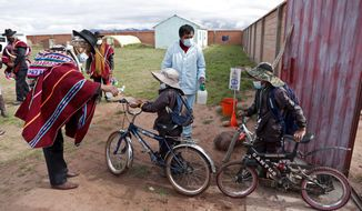 An Aymaran Indigenous parent gives anti-bacterial gel to students entering the Jancohaqui Tana school, where students are wearing new, protective uniforms as they return for their first week of in-person classes amid the COVID-19 pandemic, near Jesus de Machaca, Bolivia, Thursday, Feb. 4, 2021. (AP Photo/Juan Karita)