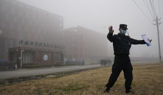 A security official moves journalists away from the Wuhan Institute of Virology after a World Health Organization team arrived for a field visit in Wuhan in China's Hubei province on Wednesday, Feb. 3, 2021. The WHO team is investigating the origins of the coronavirus pandemic has visited two disease control centers in the province. (AP Photo/Ng Han Guan)