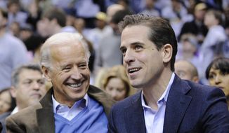 Then-Vice President Joe Biden, left, and his son Hunter Biden appear at the Duke Georgetown NCAA college basketball game in Washington on Jan. 30, 2010. (AP Photo/Nick Wass, File)